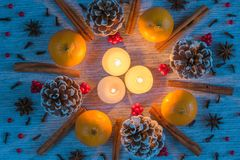 Christmas arrangement of candles surrounded by wreath of pinecones, oranges, cinnamon sticks stock photos