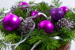 Christmas arrangement with purple balls in the wooden bowl stock photography