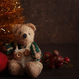Christmas arrangement with a teddy bear. And gifts near golden fir Royalty Free Stock Photo