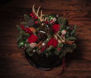 Christmas arrangement with toy reindeer, horns, flowers Royalty Free Stock Images