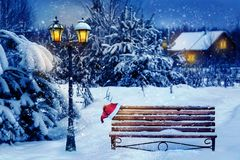Free Christmas Art Card. Santa Hat On A Bench In The Snow Against The Background Of The Christmas Winter Forest. Village House In The B Stock Photos - 156787493