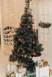 Christmas artificial tree with red balls and decor on it. Christmas and New Year`s gifts under the Christmas tree in a bright