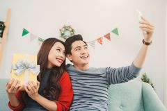 Christmas Asian Couple. A handsome man giving her girlfriend/wife a gift at home celebrating New Year People. Christmas Asian Couple. A handsome men giving her stock images