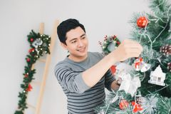 Christmas. Asian Handsome Man standing new Xmas tree at home cel Stock Photos