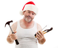 Christmas - Assembly Required. Frustrated dad in a Santa hat holding his tools. He looks scruffy, like he's been up all night assembling Christmas presents royalty free stock photos