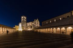 Christmas 2017 in Assisi Umbria, with a view of San Francesco. Papal church at night, with big lighted tree and people on the square royalty free stock photos