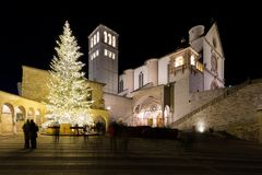 Christmas 2017 in Assisi Umbria, with a view of San Francesco. Papal church at night, with big lighted tree and people on the square royalty free stock images