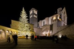 Christmas 2017 in Assisi Umbria, with a view of San Francesco. Papal church at night, with big lighted tree and people on the square stock photography