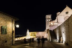 Christmas 2017 in Assisi Umbria, with a view of San Francesco. Papal church at night, with big lighted tree and people on the square royalty free stock image