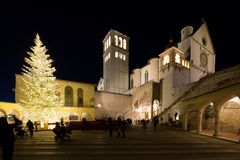 Christmas 2017 in Assisi Umbria, with a view of San Francesco papal church at night, with big lighted tree and people. On the square stock photography