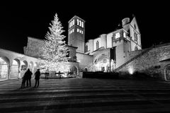 Christmas 2017 in Assisi Umbria, with a view of San Francesco. Papal church at night, with big lighted tree and people on the square stock photos
