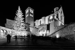 Christmas 2017 in Assisi Umbria, with a view of San Francesco. Papal church at night, with big lighted tree and people on the square stock images