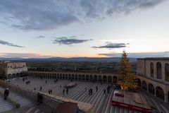 Christmas 2017 in Assisi, with a view of San Francesco papal church square at sunset, with big lighted tree, people , above a vie. W of Umbria valley stock images