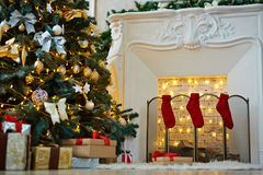 Christmas atmosphere. Decorated xmas tree, stack of gift-boxes and fireplace with red socks prepared for Christmas night Royalty Free Stock Image