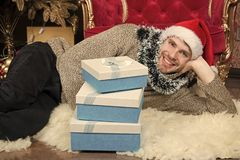 Christmas atmosphere. Man in santa hat hold xmas presents. Happy man with Christmas gift boxes. Guy is celebrating. Christmas at home. Delivery Christmas gifts stock images