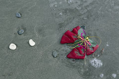 Christmas attribute washed in the sea and sand. Royalty Free Stock Photography