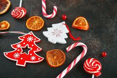 Christmas attributes. Caramelized oranges, fir branches and candy cane on dark background, Selective focus Royalty Free Stock Photos