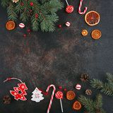 Christmas attributes. Caramelized oranges, fir branches and candy cane on dark background, Selective focus Stock Photo