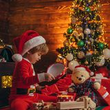 Christmas attributes. Family holiday. Childhood memories. Santa boy celebrate christmas at home. Boy child play. Christmas decorations. Merry and bright royalty free stock photo