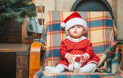 Christmas Babies. Cute little baby child on Christmas tree background. Little baby girl with a Christmas gift on wooden. Background. Happy children stock photography