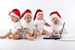 Christmas babies with laptop Stock Photo