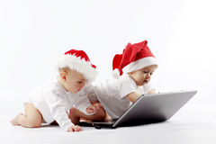 Christmas babies with laptop Royalty Free Stock Photos
