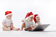 Christmas babies with laptop. Group of christmas babies playing with laptop Stock Images