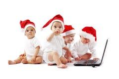 Christmas babies with laptop Stock Photos
