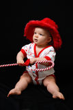 Christmas Baby. A beautiful baby portrait in a velvet Christmas hat, holding a candy-cane Stock Photos