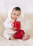 Christmas baby. Portrait of a baby, boy or girl,  sitting on sheep skin exploring presents wrapped in red paper. Christmas concept Stock Photo