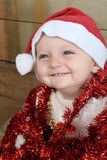 Christmas baby. Playing with decorations wearing a hat Stock Photos