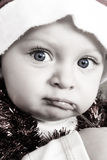 Christmas baby. Playing with decorations wearing a hat Stock Image
