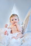 Christmas Baby Angel. Cute Baby with angel wings sitting in clouds and one vinger in her mouth, in soft colours stock photos