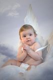 Christmas Baby Angel. Cute Baby with angel wings sitting in clouds and hands held praying Stock Photo