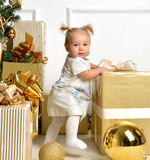 Christmas baby child toddler near gold christmas tree presents a Stock Images