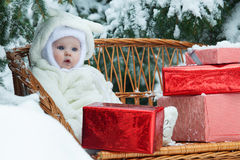 Christmas baby with gift on vinewoven bench Stock Photos