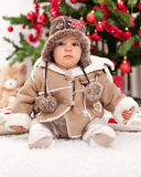 Christmas baby girl. In front of te tree Royalty Free Stock Image
