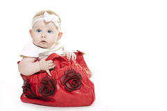 Christmas baby girl. Baby girl sitting in red bag with begraund from Christmas gift stock photo