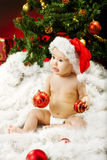 Christmas baby in hat on fur holding red ball. Christmas baby in hat sitting on fur holding red ball near new year fir tree Stock Photography