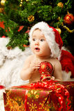 Christmas baby holding red ball near gift box. Christmas baby in hat holding red ball near gift box and new year fir tree Royalty Free Stock Photo