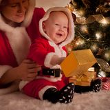 Christmas baby and mom. Open gifts under the fir tree stock image
