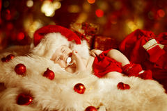Christmas Baby, New Born Kid Sleeping As Xmas Gift In Santa Hat Royalty Free Stock Photography