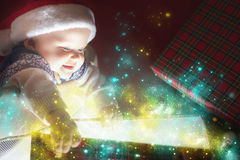 Christmas baby opening a present or gift box. Christmas baby wearing a Santa Claus hat opening a present or gift box! Night, xmas eve, surprise. Magical light Stock Images