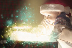 Christmas baby opening a present or gift box Stock Images
