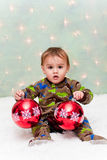 Christmas baby in pajamas holding ornaments Stock Image