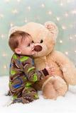 Christmas baby in pajamas holding teddy bear Stock Photos