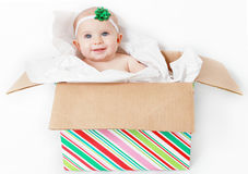 Christmas baby in present. Baby girl sitting in a Christmas present smiling at the camera stock photography