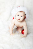 Christmas baby in red hat on fur. Christmas baby in red Santa Claus hat over white fur go on hands and knees Royalty Free Stock Image