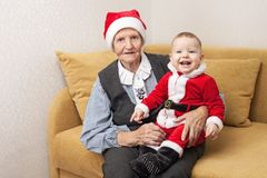 Christmas baby in Santa clothes with grandmother Stock Photography