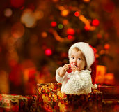 Christmas baby in Santa hat holding red ball in present gift. Christmas baby in Santa hat holding red ball in present box, Kid as Xmas gift Royalty Free Stock Image